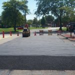 Rolling out new surface patch asphalt repairs